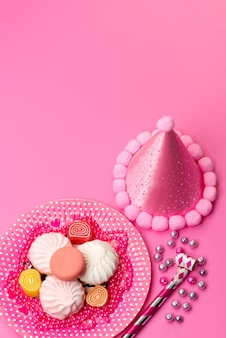 Eine draufsicht baiser und marmeladen innerhalb platte zusammen mit geburtstagspfeifen und geburtstagskappe auf rosa, eibischzucker süße farbe