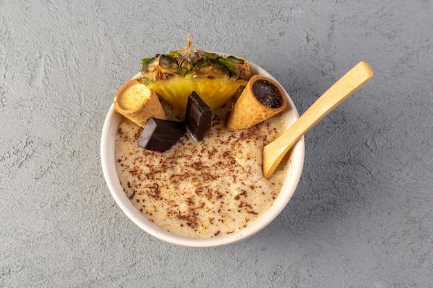 Eine draufsicht choco dessert braun mit ananasscheibe choco bars eis in weißer platte auf dem grau