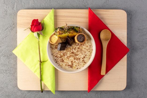 Eine draufsicht choco dessert braun mit ananasscheibe choco bars eis mit servietten rote rose in weißen platte auf der creme und grau