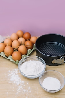 Eine draufsicht der eier im karton; zucker; mehl und backform auf hölzernen schreibtisch vor rosa hintergrund