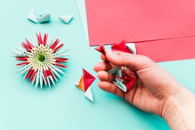 Eine draufsicht der frau, die papierblumenorigami vorbereitet