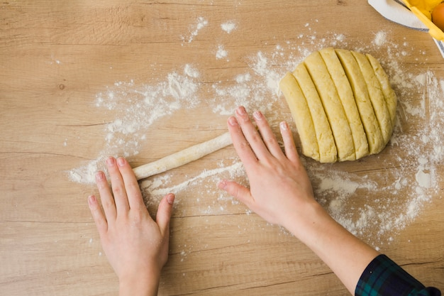 Eine draufsicht der frau, die selbst gemachten frischen italienischen teigwaren gnocchi auf holztisch zubereitet