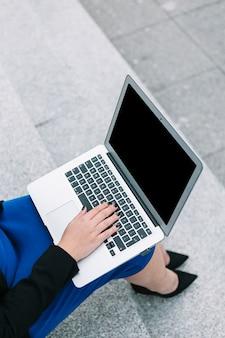 Eine draufsicht der geschäftsfrau sitzend auf dem treppenhaus, das auf laptop schreibt