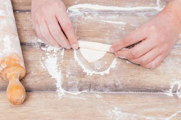 Eine draufsicht der hand eines bäckers, die den teig auf mehl über den tisch rollt