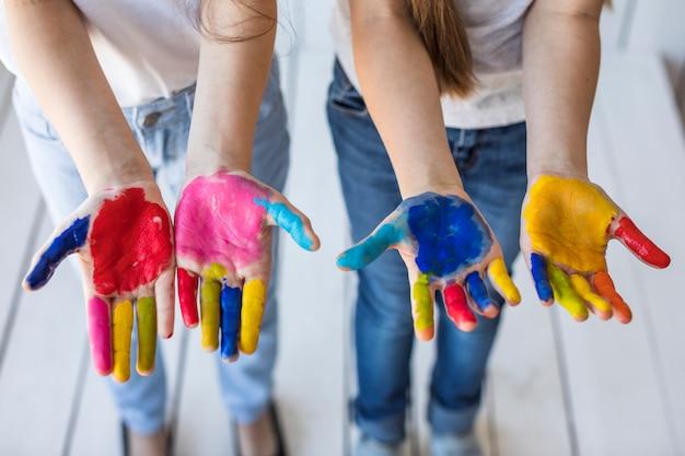 Eine draufsicht der hand von zwei mädchen, die ihre gemalten hände zeigt