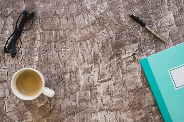 Eine draufsicht der kaffeetasse; stift; notebook und brillen auf strukturierten hintergrund