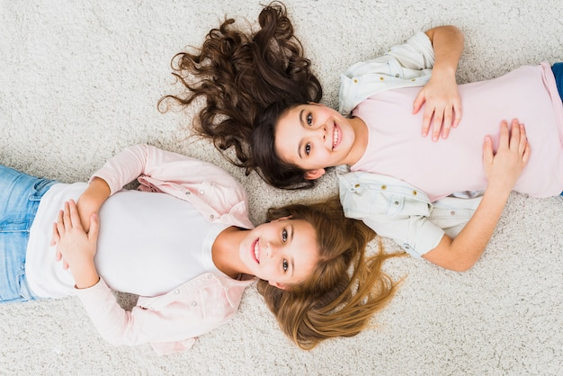 Eine draufsicht der lächelnden zwei mädchen, die auf weißem teppich sich entspannen