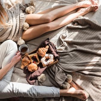 Eine draufsicht der paare, die auf bett mit frühstück auf bett sitzen