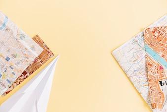 Eine Draufsicht der Stadtstraßenkarten und des Papierflugzeugs auf farbigem Hintergrund