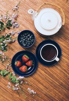 Eine draufsicht der teekanne; blaubeeren; kaffeetasse; und erdbeere mit blumen auf hölzernem hintergrund