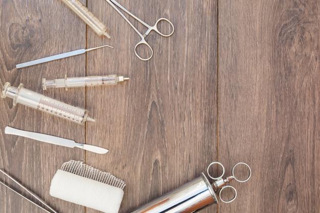 Eine draufsicht der vintage-edelstahlspritze; otoskop und medizinische geräte auf hölzernen schreibtisch