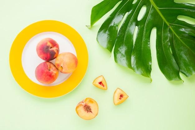 Eine draufsicht des ganzen pfirsichs auf platte mit scheiben und grünem monstera-blatt auf pastellhintergrund