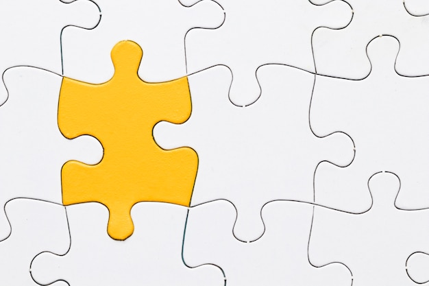 Eine draufsicht des gelben puzzlespiels unter weißem stück