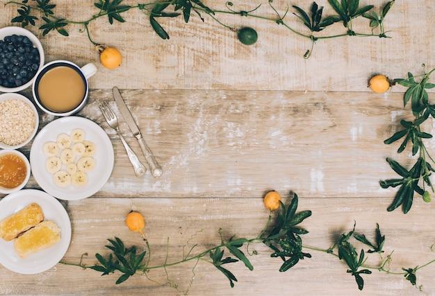 Eine draufsicht des gesunden frühstücks und der kaffeetasse mit efeu auf holztisch