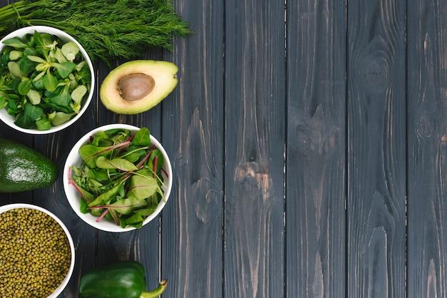 Eine draufsicht des grünen gemüses auf schwarzem hölzernem schreibtisch