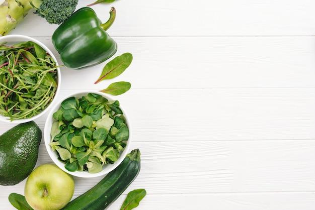 Eine draufsicht des grünen gesunden frischgemüses auf weißem hölzernem schreibtisch