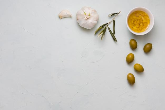 Eine draufsicht des hineingegossenen olivenöls und des knoblauchs in der schüssel auf konkretem hintergrund
