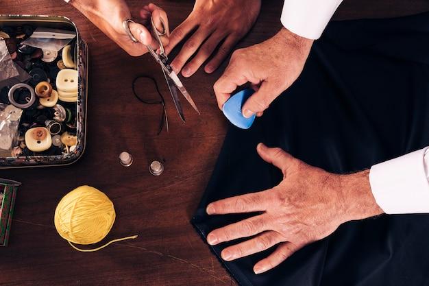 Eine draufsicht des männlichen modedesigners und seines assistenten, die in der werkstatt arbeiten