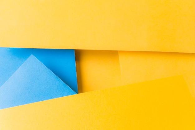 Eine draufsicht des strukturierten hintergrundes des gelben und blauen papiers