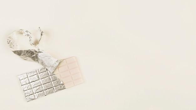 Eine draufsicht des weißen schokoriegels mit einer offenen verpackung
