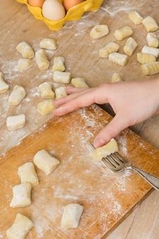 Eine draufsicht einer person, die den teigwaren-gnocchi-teig auf schneidebrett zubereitet