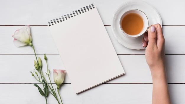 Eine draufsicht einer person, die tasse tee mit leeren notizblock- und eustomablumen hält