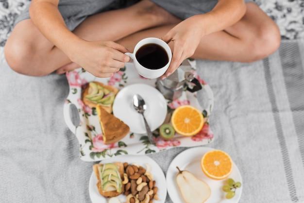 Eine draufsicht eines jungen, der auf dem bett hält kaffeetasse sitzt