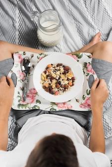 Eine draufsicht eines jungen, der auf dem bett mit dem gekreuzten bein isst, das gesunde hafermahlzeit hat