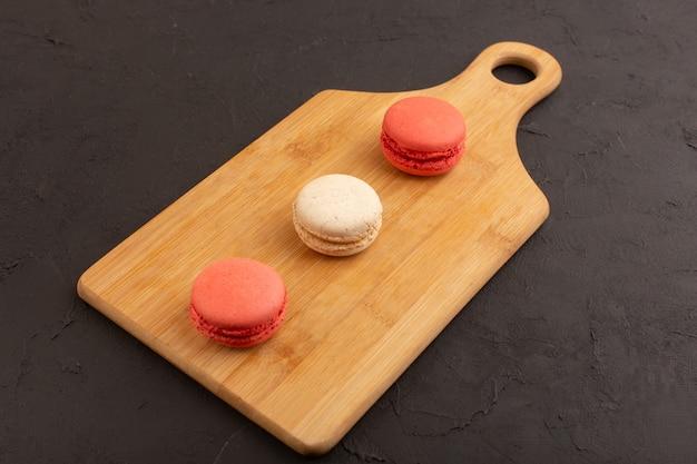 Eine draufsicht färbte französische macarons, die auf dem dunklen tischkuchenkekszuckersüß köstlich sind