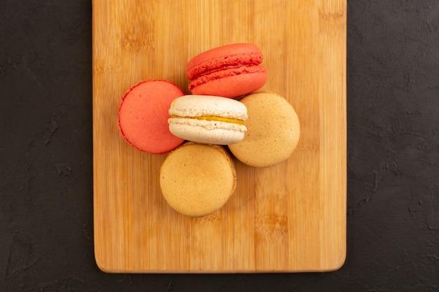 Eine draufsicht färbte französische macarons köstlich und lecker auf dem hölzernen schreibtisch und dem dunklen tisch