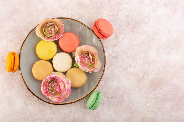 Eine draufsicht färbte französische macarons mit blumen innerhalb platte auf dem rosa schreibtischkuchen-kekszuckersüß