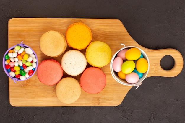 Eine draufsicht färbte französische macarons mit leckeren bonbons