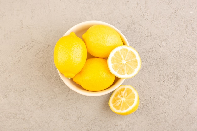 Eine draufsicht frische zitronen sauer reif ganze milde zitrus tropisches vitamin gelb zusammen mit getrockneten blumen auf dem cremefarbenen schreibtisch