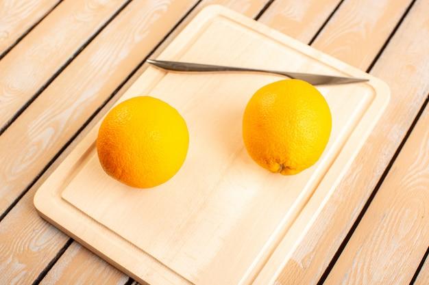 Eine draufsicht frische zitronen saure reife milde zitrusfrucht saftiges tropisches vitamingelb auf dem cremefarbenen rustikalen schreibtisch
