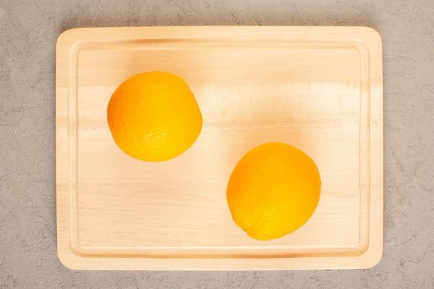 Eine draufsicht frische zitronen saure reife milde zitrusfrucht saftiges tropisches vitamingelb auf dem cremefarbenen schreibtisch