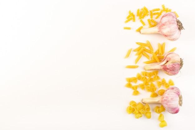 Eine draufsicht ganze knoblauchzehen reifen frisch isoliert ausgekleidet zusammen mit italienischer pasta-sammlung auf dem weißen hintergrund gemüselebensmittel mahlzeit zutat