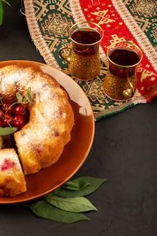 Eine draufsicht gebackene obstkuchen köstliche runde mit roten kirschen innen und zuckerpulver innen runde braune platte zusammen mit tee auf dunkel