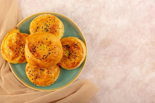 Eine draufsicht gebackene qogals rund geformte leckere heiße frisch aus dem ofen innerhalb der grünen platte