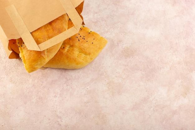 Eine draufsicht gebackenes brot heißes leckeres frisches innerhalb der papierverpackungen auf rosa