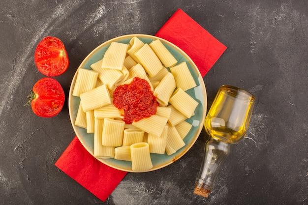 Eine draufsicht gekochte italienische nudeln mit tomatensauce innerhalb platte mit olivenöl