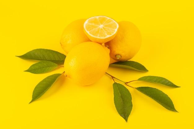 Eine draufsicht gelbe frische zitronen frisch reif ganz und geschnitten zusammen mit grünen blättern früchte isoliert auf der gelben hintergrund zitrusfrucht farbe