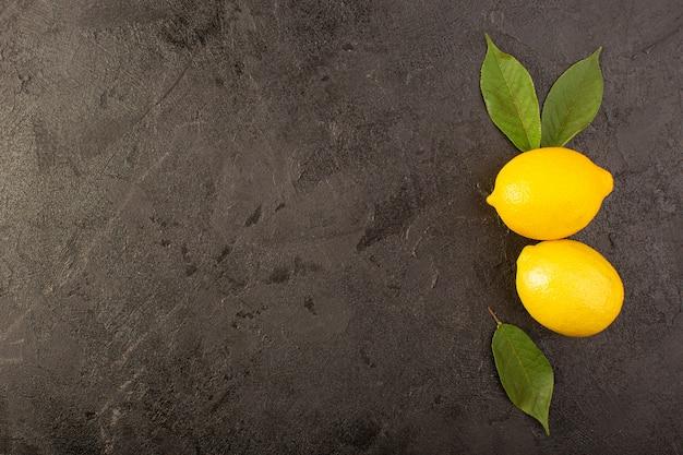 Eine draufsicht gelbe frische zitronen weich und saftig ganz und geschnitten mit grünen blättern auf dem dunklen hintergrund früchte zitrusfarbe