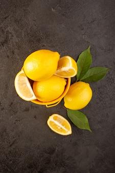 Eine draufsicht gelbe frische zitronen weich und saftig ganz und in gelben korb geschnitten mit grünen blättern auf dem dunklen hintergrund früchte zitrusfarbe verteilt
