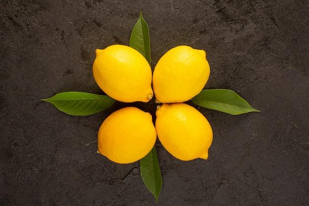 Eine draufsicht gelbe ganze zitronen frisch saftig sauer mild mit grünen blättern isoliert auf der dunklen hintergrund zitrusfrucht farbzusammensetzung