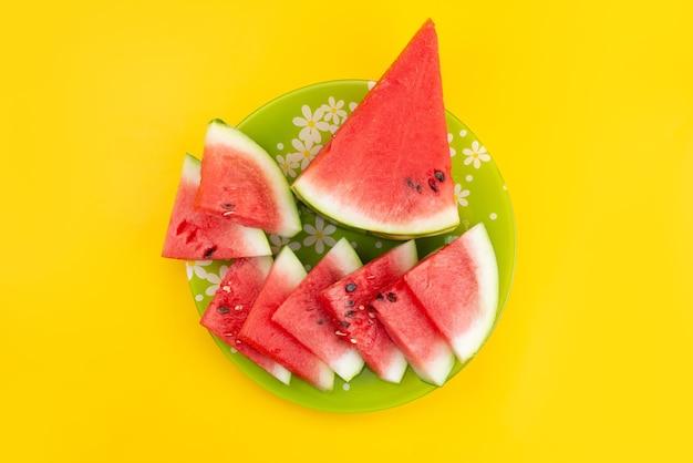 Eine draufsicht geschnittene frische wassermelone saftig und weich auf gelbem schreibtisch, fruchtsommerfarbe