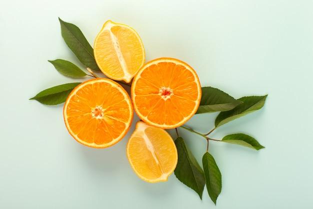 Eine draufsicht geschnittene orange frische reife saftige milde isolierte halb geschnittene stücke zusammen mit geschnittenen zitronen und grünen blättern auf dem weißen hintergrund fruchtfarbe zitrusfrüchte