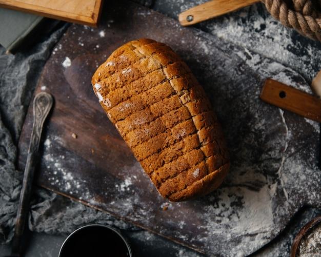 Eine draufsicht geschnittenes graues brot, das auf dem grauen schreibtischbrotbrötchen-essensteig gebacken wurde
