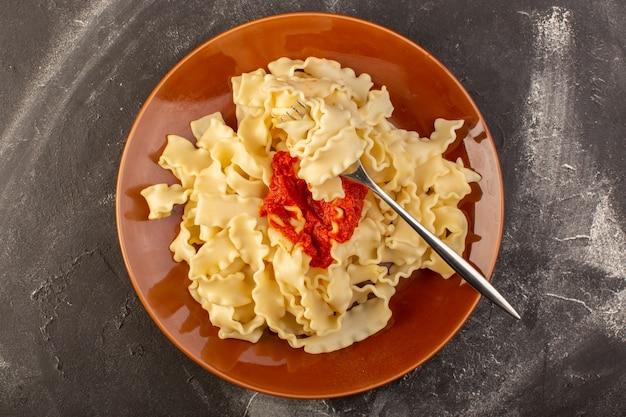 Eine draufsicht kochte italienische nudeln mit tomatensauce innerhalb platte