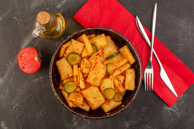 Eine draufsicht kochte italienische nudeln mit tomatensauce und gurke in der pfanne