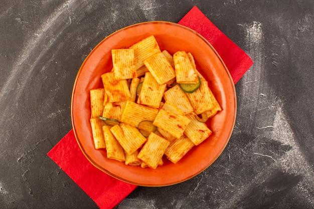 Eine draufsicht kochte italienische nudeln mit tomatensauce und gurke innerhalb platte